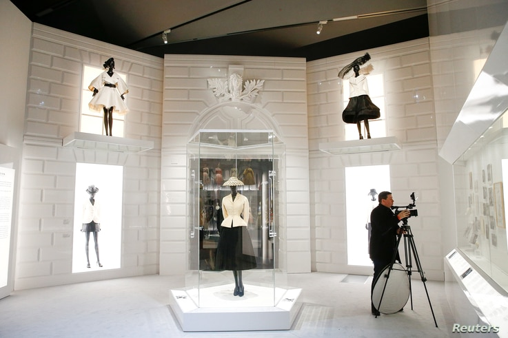 """A person photographs creations during a photocall for the """"Christian Dior: Designer of Dreams"""" exhibition at the Victoria & Albert (V&A) Museum in London, Jan. 30, 2019."""