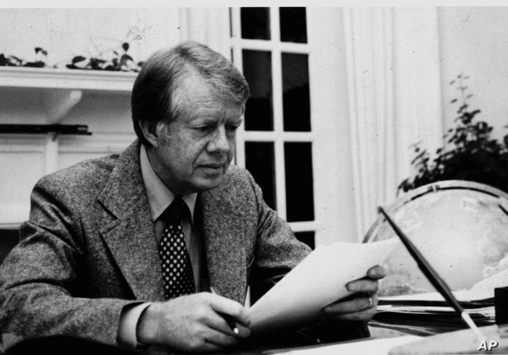 President Jimmy Carter is shown in this White House photo at work in the White House's Oval Office in 1977.  (AP Photo/White House/files)