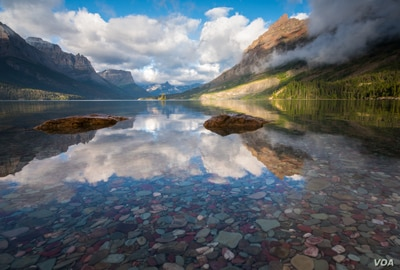 Sky and mountains reflecting on St. Mary's Lake in Glacier National Park, Montana. (Photo by David Fortney, Courtesy of MacGillivray Freeman Films)
