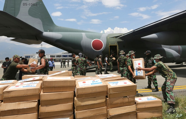Indonesian and Japanese military personnel unload relief aid from a Japan Air Force cargo plane at the Mutiara Sis Al-Jufri airport in Palu, Central Sulawesi, Indonesia, Oct. 6, 2018.