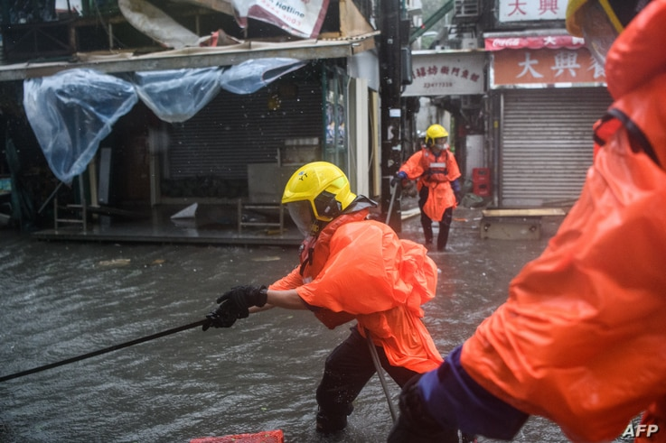 Fire rescue members prepare a rope to help people cross a flooded street at the village of Lei Yu Mun during Typhoon Mangkhut in Hong Kong, Sept. 16, 2018.