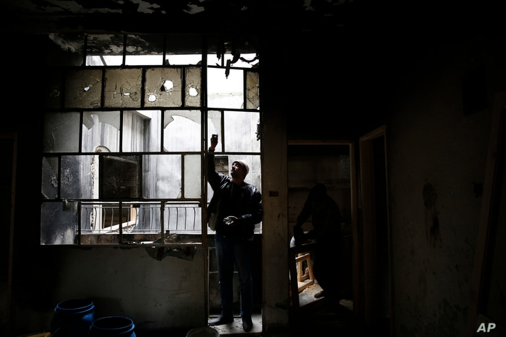 Mohammed Bayraqdar removes broken window glass at his burned house in Khaldiyeh, one of the worst damaged neighborhoods in Homs, Syria, Jan. 17, 2018.