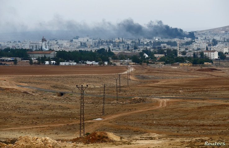Smoke rises from the Syrian town of Kobani, seen from near the Mursitpinar border crossing on the Turkish-Syrian border in the southeastern town of Suruc in Sanliurfa province, Oct. 17, 2014.