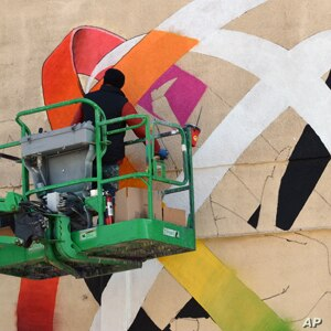 Ukrainian artist Vladimir Manzhos at work on his mural.