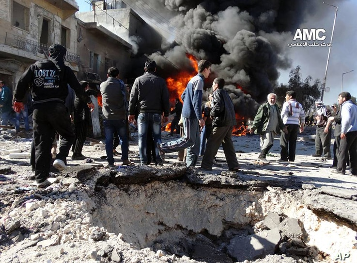 This citizen journalism image provided by the Aleppo Media Center (AMC), an anti-Bashar Assad group, shows people gathering near flames after a Syrian government forces warplane attack in al-Bab, Aleppo, Feb. 1, 2014.