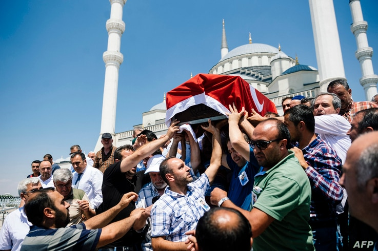 People carry the coffin of victim of the coup attempt Sehidmiz Murat Inci during his funeral ceremony at the Kocatepe Mosque in Ankara on July 18, 2016.