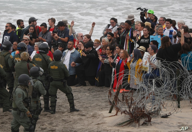 U.S. police and Border Patrol hold a line as members of an inter-faith group, showing support for Central American asylum-seekers who arrived in recent caravans and calling for an end to detaining and deporting immigrants, pray during a protest in Sa...