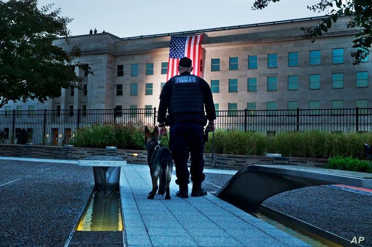 At the Pentagon Memorial a K-9 officer pauses as he looks toward the U.S. flag as it is draped on the side of the Pentagon where the building was attacked on September 11th in 2001, on the 14th anniversary of the attack, Sept. 11, 2015, in Washington...