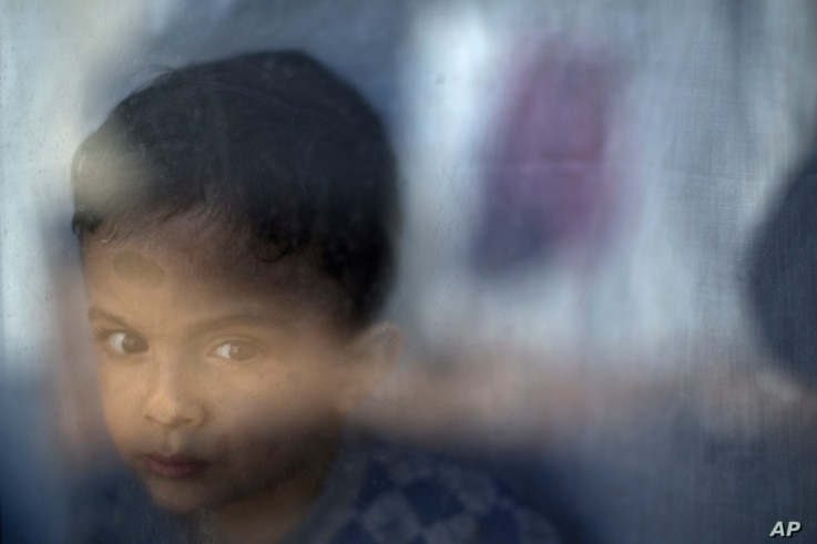 Migrant Petram Mehdi, 2, from Tehran, Iran, stands by the window of his family's shelter at the refugee camp of Ritsona about 86 kilometers (53 miles) north of Athens, Jan. 12, 2017.