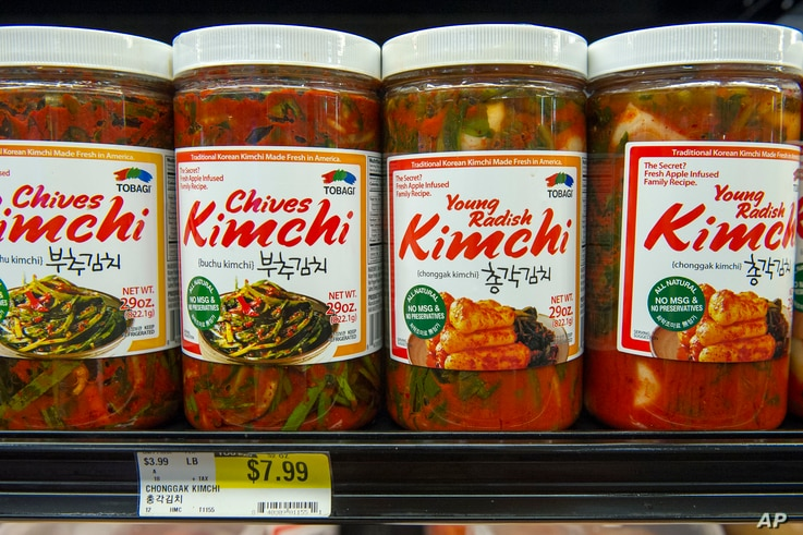 FILE - Different flavors of Korean Kimchi are displayed in a cooler at the Super H Mart Asian grocery in Fairfax, Virginia, July 20, 2015. Classic Korean food items are showing up with more frequency on American menus and grocery shelves.