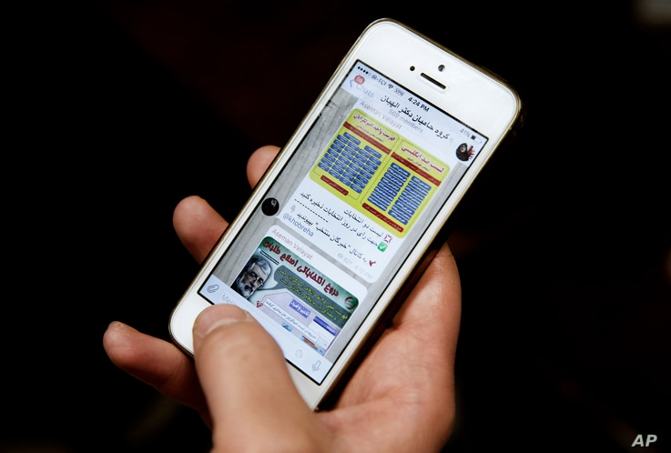 FILE - An Iranian man shows Telegram app messages on his mobile phone in Tehran, Feb. 24, 2016.