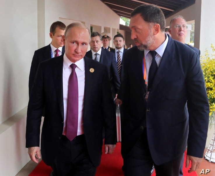 FILE - Russia's President Vladimir Putin (L) and Russian metals magnate Oleg Deripaska (R) walk to attend the APEC Business Advisory Council dialogue in Danang, Vietnam, Nov. 10, 2017.