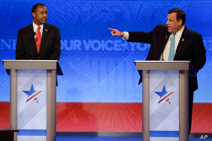 New Jersey Gov. Chris Christie  points toward Republican presidential candidate, Sen. Marco Rubio at the other end of the stage as retired neurosurgeon Ben Carson looks on