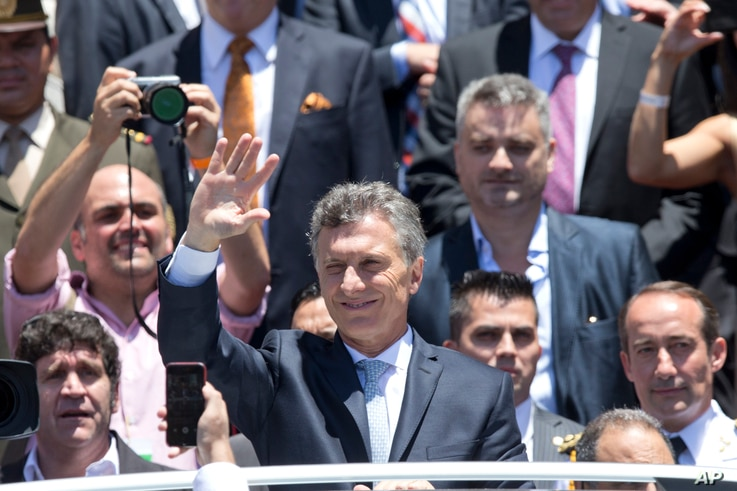 Argentina's President Mauricio Macri waves to followers as he leaves Argentina's Congress after he was sworn in, in Buenos Aires, Dec. 10, 2015.