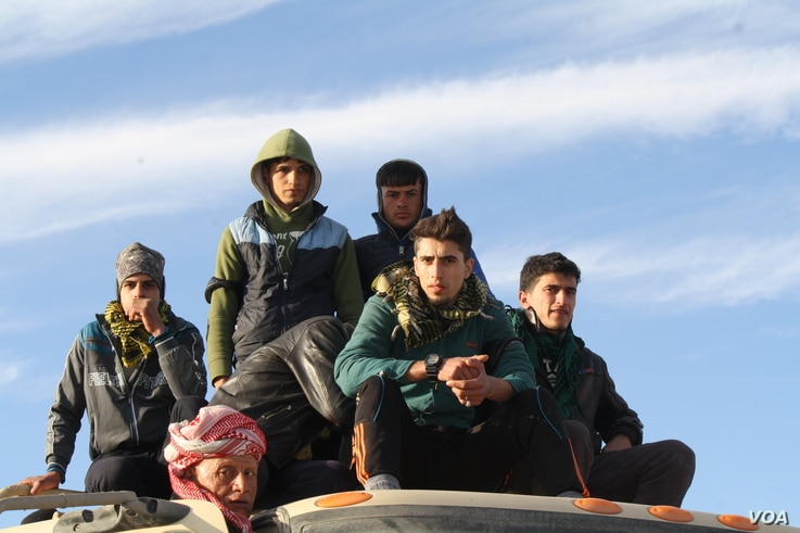 Young men, like this group on top of an army truck fleeing Mosul, say more men got married under IS, in fear that they would not be able to follow IS rules and get caught talking or texting with a woman. (H. Murdock/VOA)