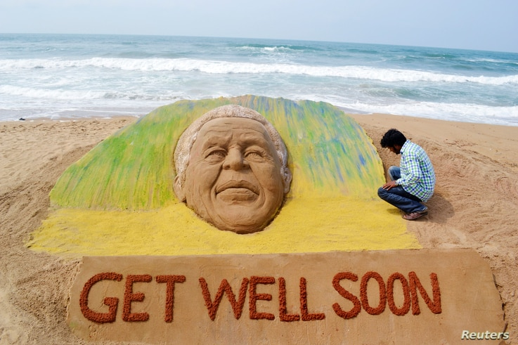 Artist Sudarshan Pattnaik works on a sand sculpture created in the likeness of former South African President Nelson Mandela, to wish him a speedy recovery, in Puri, India, June 9, 2013.