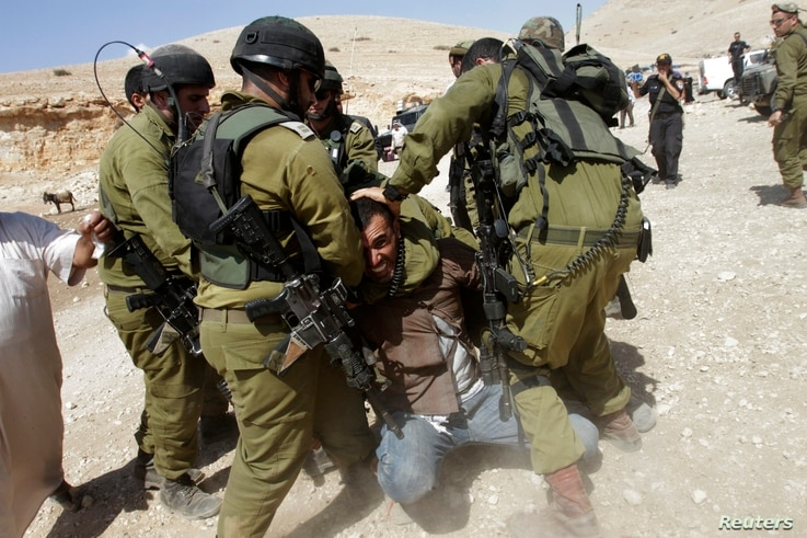 Israeli soldiers detain Palestinian manduring scuffles following EU diplomats' attempt to deliver aid to West Bank herding community of Khirbet al-Makhul, Sept. 20, 2013.