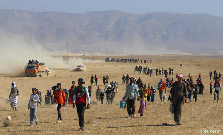 Displaced people from the minority Yazidi sect, fleeing violence from forces loyal to the Islamic State in Sinjar town, walk towards the Syrian border, on the outskirts of Sinjar mountain, near the Syrian border town of Elierbeh of Al-Hasakah Governo