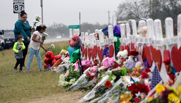 Christina Osborn and her children Alexander Osborn and Bella Araiza visit a makeshift memorial for the victims of the shooting at Sutherland Springs Baptist Church, Nov. 12, 2017, in Sutherland Springs, Texas.