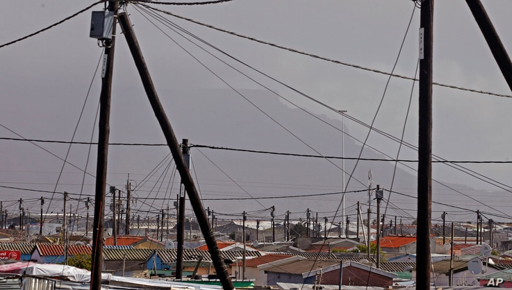 FILE - A view of electrical poles and wires at a suburb, with Table Mountain in backdrop, near the city of Cape Town, South Africa, Sept. 27, 2013.