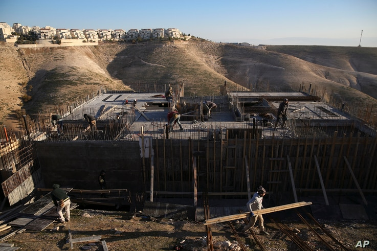Palestinian laborers work at a construction site in a new housing project in the Israeli settlement of Maale Adumim, near Jerusalem, Feb. 7, 2017.