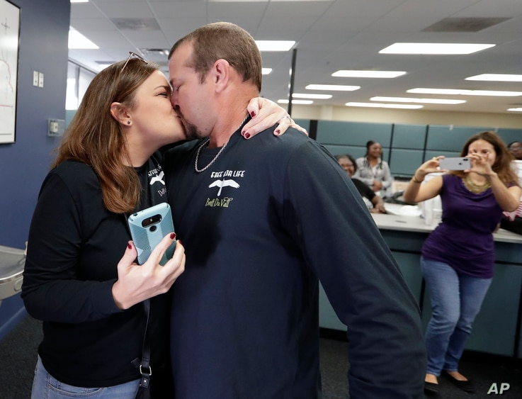 Former felon Brett DuVall, right, kisses his wife Dottie as they celebrate after he registered to vote at the Supervisor of Elections office Tuesday, Jan. 8, 2019, in Orlando, Fla.