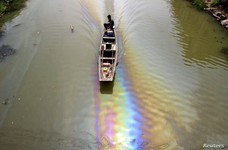 FILE - A man drives a boat along a river polluted by leaked fuel in Shaoxing, Zhejiang province, China, April 29, 2015.