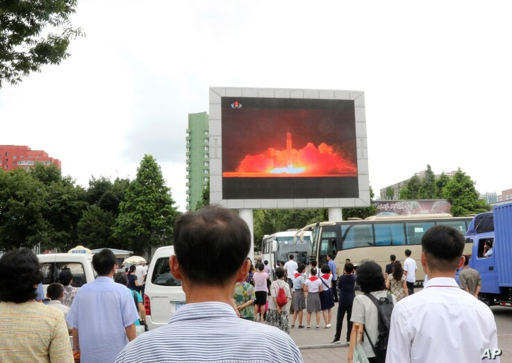 People watch a news broadcast about a missile launch in Pyongyang, North Korea, July 29, 2017. North Korean leader Kim Jong Un says the second flight test of an intercontinental ballistic missile demonstrated his country can hit the U.S. mainland.