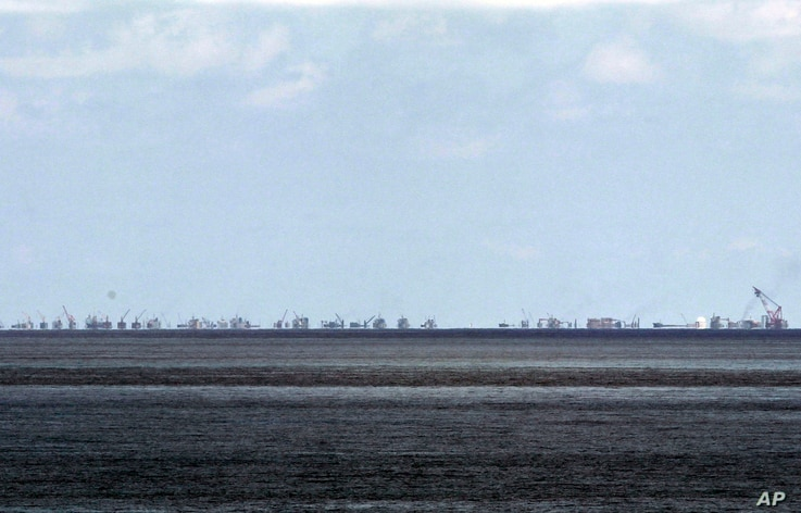 FILE - The alleged on-going reclamation of Subi Reef by China is seen from Pag-asa Island in the Spratly Islands in the South China Sea, western Palawan Province, Philippines, May 2015.