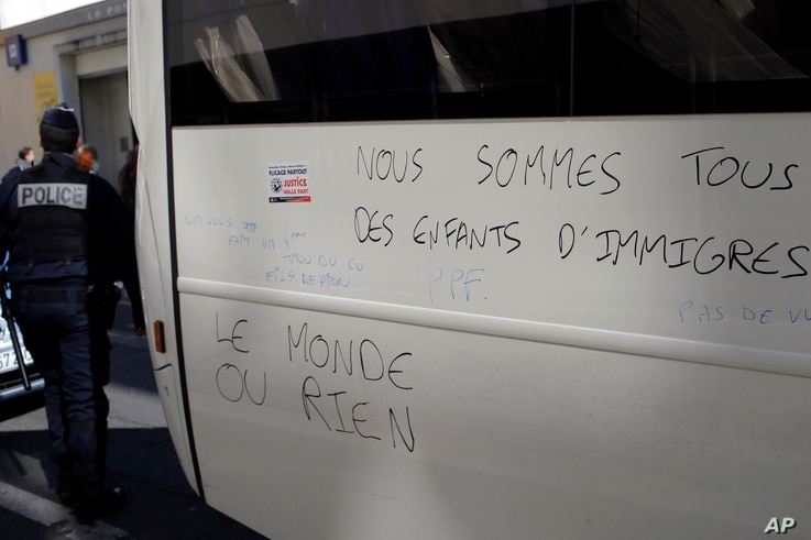 "France Migrants: Police officer walks by a graffiti reading ""We Are All Migrants' Children, The World or Nothing"" after they evacuate migrants camped out in the empty Jean Jaures school in northeast Paris, France, Wednesday, May 4, 2016."