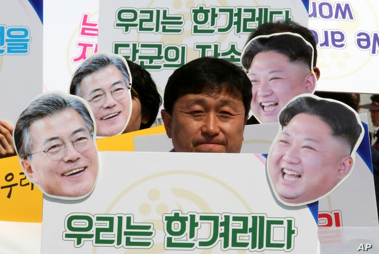 """An activist with cutouts of South Korean President Moon Jae-in, left, and North Korean leader Kim Jong Un participates  in a rally welcoming the planned summit between South and North Korea in Seoul, South Korea, April 25, 2018. The signs read: """" We ..."""