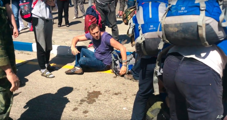 In this frame from video provided by Anapa Today, opposition leader Alexei Navally, center, tries to get up after being attacked at the Anapa airport, southern Russia, May 17, 2016.
