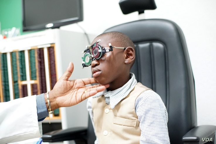 Lemuel Tebuck, now 8 years old, with aligned eyes from strabismus surgery, undergoes a regular check-up at Yaoundé Central Hospital, Yaoundé, Cameeroon, April 2016.