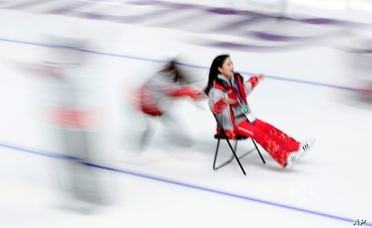 A volunteer pushes another volunteer on a chair on the ice after the last speedskating race at the Gangneung Oval at the 2018 Winter Olympics in Gangneung, South Korea, Feb. 24, 2018.