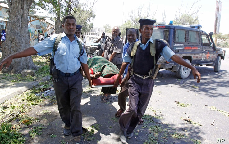 Police officers carry a body after a suicide bomber blew himself up near a restaurant in Mogadishu, Feb. 27, 2014.