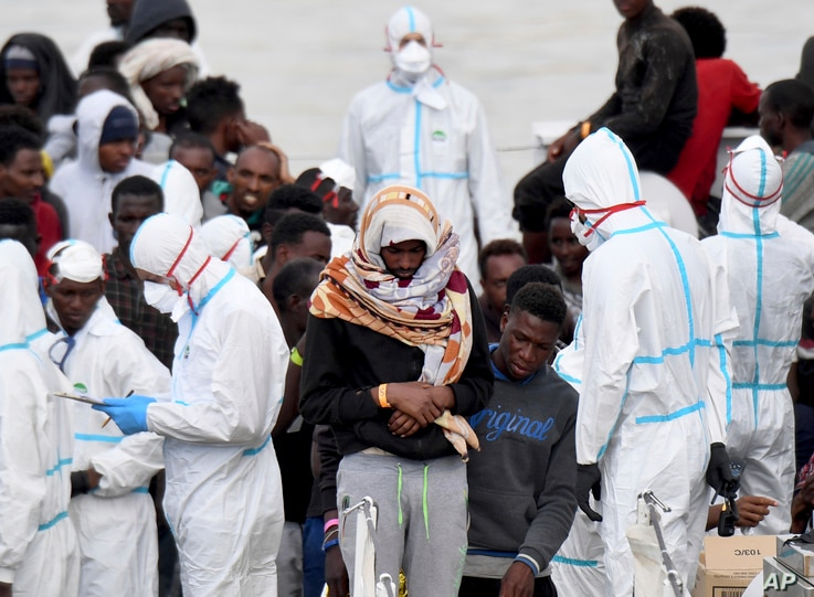 "Migrants wait to disembark from Italian Coast Guard vessell ""Diciotti"" as it docks at the Sicilian port of Catania, southern Italy, June 13, 2018."