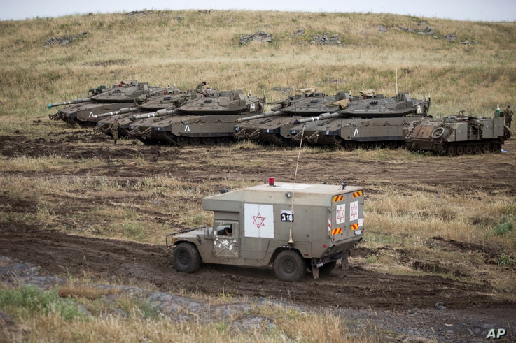 An Israeli military ambulance drives past tanks in the Israeli-controlled Golan Heights, near the border with Syria, May 10, 2018.