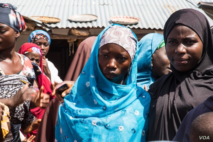 Fourteen-year-old Basira Bello (with blue hijab) is escorted by a female relative to the home of her soon-to-be husband. (C. Oduah/VOA)