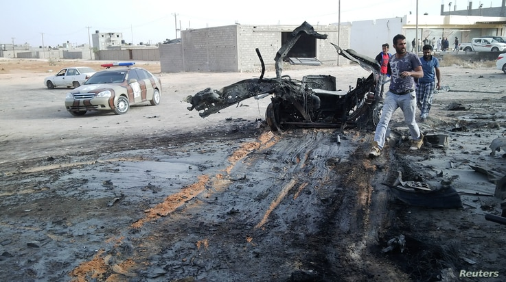 People inspect the site after a car bomb hit the convoy of Abdel-Razeq Nathouri, the chief of staff of the eastern Libyan military, outside Benghazi, Libya,  April 18, 2018.