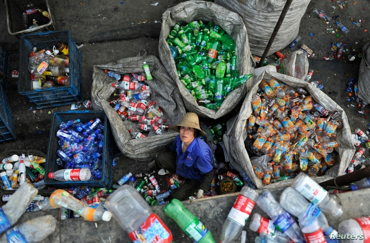 A laborer looks up as she sorts plastic bottles at a garbage recycling centre in Hefei, Anhui province, China, May 20, 2014.