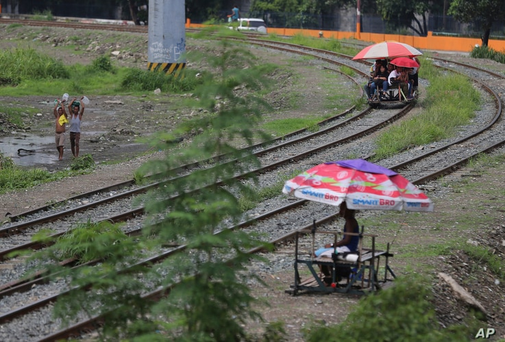 FILE - Filipino students ride a metal-wheeled cart with benches fashioned from scrap wood for 10 pesos (about US 20 cents) each for a ride along the railway in Manila, Philippines, Aug. 12, 2015. Manila and other cities are choked with construction s...