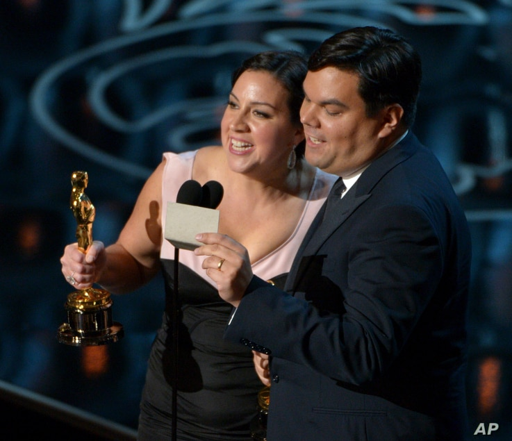"""Kristen Anderson-Lopez, left, and Robert Lopez accept the award for an original song in a feature film for """"Let It Go"""" from """"Frozen"""" during the Oscars at the Dolby Theatre on March 2, 2014, in Los Angeles.  (Photo by John Shearer/Invision)"""