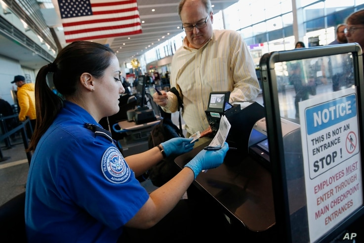 Transportation Security Administration officer Darby Finch checks boarding passes and identification at Logan International Airport in Boston, Dec. 23, 2018.