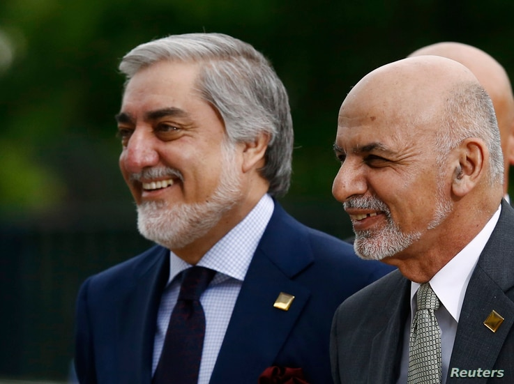 FILE - Afghanistan's President Ashraf Ghani, right, and Chief Executive Abdullah Abdullah arrive for a NATO summit in Warsaw, Poland, July 9, 2016.