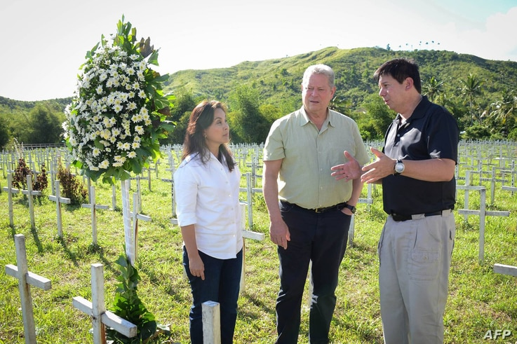 This photo taken on March 12, 2016 shows former US vice-president Al Gore (C) talking to Philippine Senator Loren Legarda (L) and Mayor Alfred Romualdez during a visit to the mass grave for victims of super typhoon Haiyan, in Tacloban City, central P...