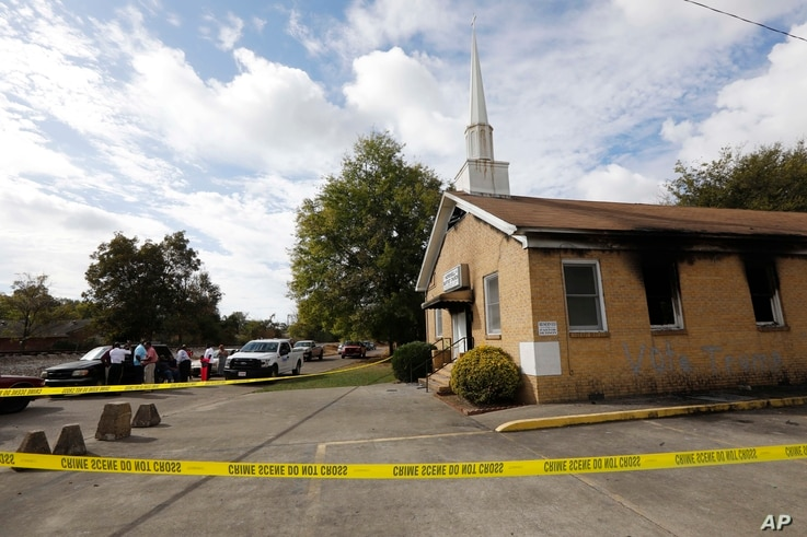 """Area residents and church members look on as authorities investigate a fire at Hopewell Baptist Church in Greenville, Mississippi, Nov. 2, 2016. """"Vote Trump"""" was spray-painted on an outside wall of the African American church."""