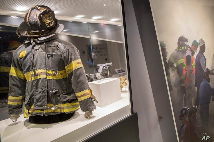 The helmet and turnout coat, left, belonging to firefighter Jonathan Ielpi and the badge and gun belonging to police officer John Perry, who both died during the terrorist attacks on the World Trade Center, are on display at the 9/11 Tribute Museum i...