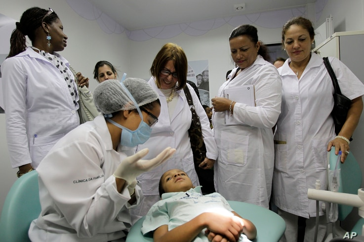 FILE - In this Aug. 30, 2013 file photo, Cuban doctors observe a dental procedure during a a training session at a health clinic in Brasilia, Brazil.