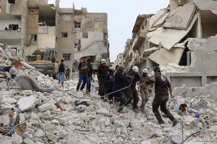 Civil defense members work at a site hit at dawn by an airstrike in the rebel-controlled town of Ariha in Idlib province, Syria, Feb. 27, 2017.