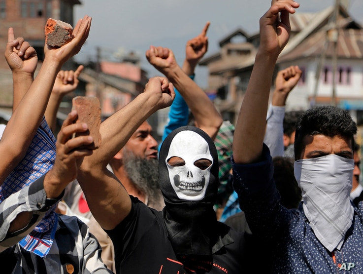 Masked Kashmiri protesters hold bricks as they shout freedom slogans in Srinagar, India, May. 27, 2017. One civilian was killed and dozens of others injured Saturday after massive anti-India protests and clashes erupted in Indian-controlled Kashmir f